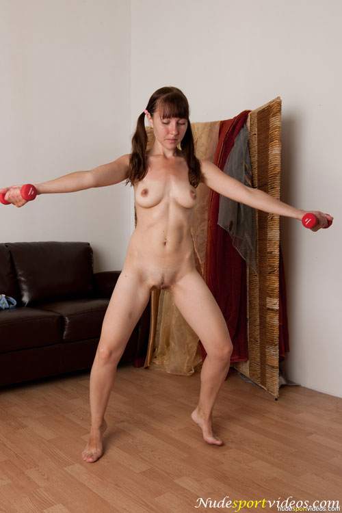 Nude fitness balancing on the tiptoes with dumbbells
