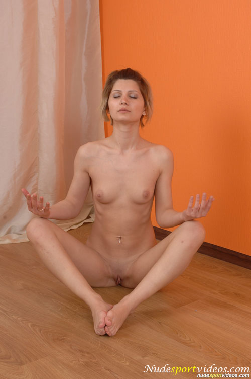 Seated nude yoga pose by a flexible girl