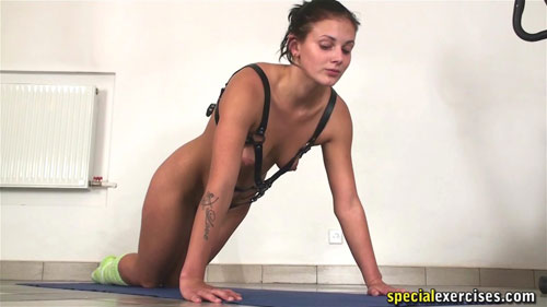 Submissive trainee in the lesdom harness does the knelt pushups